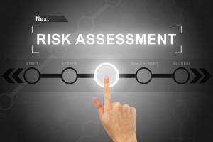 hand clicking risk assessment button on a screen interface